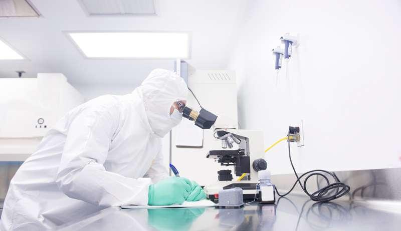 Medical Individual Looking through Microscope